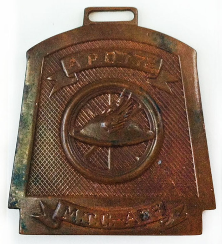 This World War I medallion bears the American Expeditionary Force's Motor Transport Corps' emblem of a feather stuck in an infantry helmet, which is in front of a wheel. It is engraved: A.P.O. 772 M.T.C. – AEF. (U.S. Air Force photo)
