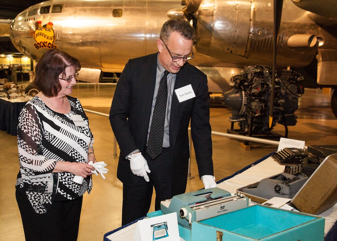 Museum Deputy Director/Senior Curator Krista Strider shows actor Tom Hanks a presidential typewriter from Air Force One (SAM 26000) at the National Museum of the U.S. Air Force in April 2016. (U.S. Air Force photo by Ken LaRock)