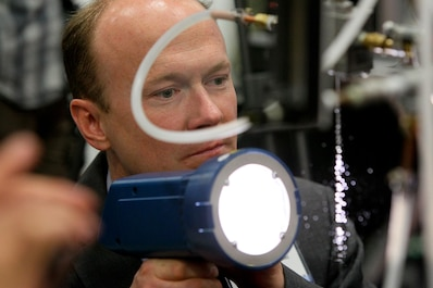 160217-N-HW977- SAN DIEGO, Calif. (Feb. 17, 2015) Dr. Aaron Wiest, a Naval Surface Warfare Center (NSWC), Corona Division physicist, points a strobe light at bubble-filled water droplets during WEST 2016, a three-day conference co-sponsored by Armed Forces Communications and Electronics Association (AFCEA) and U.S. Naval Institute (USNI). Earlier Rear Adm. Lorin Selby, NSWC commander, highlighted the intellectual capital of the warfare centers and their capability to deliver innovative technology to the warfighter. (U.S. Navy photo by Greg Vojtko/Released)