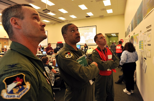 From left, U.S. Air Force Col. Jeff Fiebig, the mobilization assistant to the commander of 1st Air Force, Maj. Gen. Garry Dean, the joint force air component commander for North American Aerospace Defense Command and U.S. Northern Command, and Coast Guard Cmdr. Drew Cromwell, air operations branch chief for the Houma Incident Command Post, analyze safety information in the central operations room of the command post in Houma, La., June 15, 2010. Dean visited the command post to discuss ways the Air Force can assist in the Gulf of Mexico during the oil spill response efforts to the Deepwater Horizon oil spill. (DoD photo by Petty Officer 3rd Class Robert Brazzell, U.S. Coast Guard/Released)