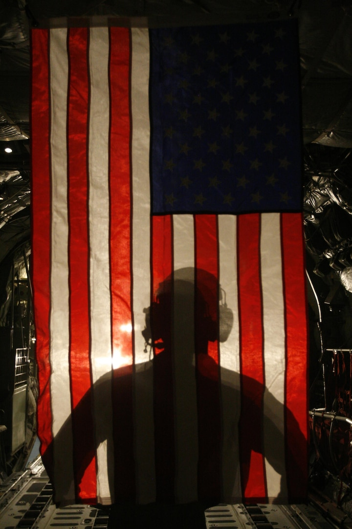 U.S. Marine Corps Corporal Jacob Hall, a crew chief with Marine Aerial Refueling Transportation Squadron 352, stands in front of an American Flag after a battlefield illumination mission aboard Camp Bastion, Afghanistan, July 18, 2014. Battlefield illumination missions were implemented to light up areas in support of nighttime coalition operations within Regional Command (Southwest). (DoD photo by Sgt. Frances Johnson, U.S. Marine Corps/Released)