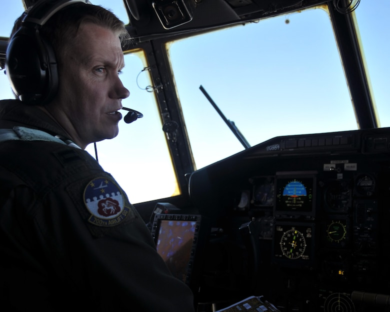 Capt. Jamie Atkinson, 700th Airlift Squadron C-130 aircraft commander, talks with the crew on the flight deck of the C-130 shortly after taking off from Aviano Air Base, Italy on April 11, 2016. The C-130 carried a fully-armored humvee, which it airdropped over Hohenfels Training Area, Germany. (U.S. Air Force photo/ Senior Airman Andrew J. Park)