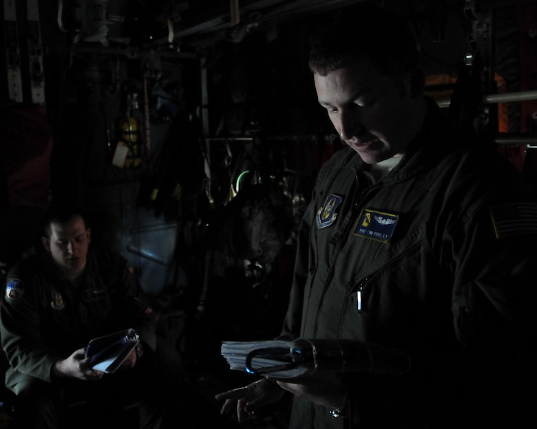 Staff Sgt. Tim Ousley, 700th Airlift Squadron loadmaster, briefs the airdrop checklist to SeniorAirman Brad Johnson, 700th AS loadmaster, in the cargo area of a C-130 Hercules at Aviano Air Base, Italy on April 11, 2016. The checklist provides a step-by-step process for preparing the C-130 for conducting airdrops. (U.S. Air Force photo/ Senior Airman Andrew J. Park)