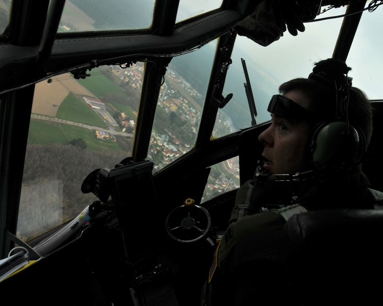 Capt. Mike Terrell, 700th Airlift Squadron C-130 instructor pilot, looks out the window of a C-130 Hercules as he makes a sharp turn flying over Germany on April 12, 2016. The C-130 made several passes over Hohenfels Training Area, Germany so that all the paratroopers could jump from the plane. (U.S. Air Force photo/ Senior Airman Andrew J. Park)