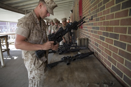 Lance Corporal Royce Cappucilli, with 2nd Platoon, Charlie Company, Fleet Anti-Terrorism Security Team, Marine Corps Security Forces Regiment, inspects his weapon before turning it in to the armory aboard Camp Allen, in Norfolk, Virginia, 13 April, after returning from a four-month deployment to Guantanamo Bay, Cuba. The Marines from Charlie Company posted security along the fence line and stood post in guard towers at Guantanamo Bay Naval Base, while conducting land navigation exercises, going to rifle and weapons ranges and engaging in weapons system sustainment training. (U.S. Marine Corps photo by Cpl. Calvin Shamoon/Unreleased)