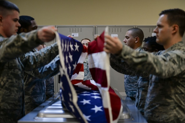 Honor guardsmen in training work with experienced members to practice properly removing a flag from a casket at Mountain Home Air Force Base, Idaho, March 3, 2016. The base honor guard does roughly 300 deatils a year, mostly consisting of funerals. (U.S. Air Force photo by Senior Airman Jessica H. Evans/RELEASED)