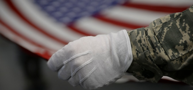 A new honoe guardsman practices folding a flag while wearing gloves at Mountain Home Air Force Base, Idaho, March 3, 2016. Honor guard's top priority is to make sure fallen veterans are rendered proper military honors. (U.S. Air Force photo by Senior Airman Jessica H. Evans/RELEASED)