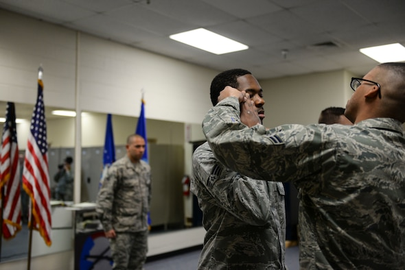 Base honor guard flight lead, Senior Airman Radames Rivera Rodriguez critiques potential honor guardsmen as older members perfect their salute at Mountain Home Air Force Base, Idaho, March 3, 2016. For Rivera, letting go of basic training techniques and learning to perfect rifle manuevers was most difficult for him as a new honor guardsman. (U.S. Air Force photo by Senior Airman Jessica H. Evans/RELEASED)