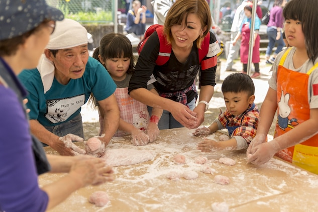 Japanese civilains roll mochi into balls during a Mochitsuki – rice pounding – event with residents from Marine Corps Air Station Iwakuni at Tenno Elementary School in Tenno, Japan, April 16, 2016. Commonly eaten during the Japanese New Year and festivals, mochi is made when glutinous rice is soaked, steamed and pounded with a wooden mallet and mortar, forming a sticky, stretchy texture. The rice is then rolled in flour and molded into round shapes to form mochi or rice cakes, which participants enjoyed in Japanese miso-based vegetable soup. (U.S. Marine Corps photo by Lance Cpl. Aaron Henson/Released)