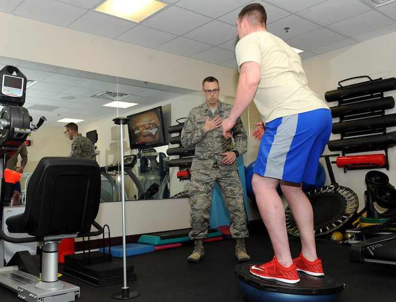 Tech. Sgt. Sean Devereaux, 22nd Medical Operations Squadron NCO in charge of physical training, helps an Airman with his balance, April 19, 2016, at McConnell Air Force Base, Kan. The medical group is approaching health care in a more proactive way by performing lower extremity screenings and analyzing the way Airmen walk or run in order to prevent future problems. (U.S. Air Force photo/Senior Airman David Bernal Del Agua)
