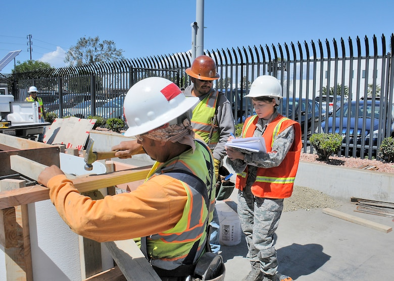 "Senior Airman Gladys Pargas, a ""Gate keeper"" for the construction project, discusses the checklist with workers. (U.S Air Force photo/Joe Juarez)"