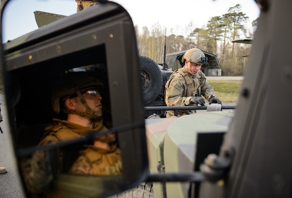 """A member of the 435th Contingency Response Group watches as a fellow Airman prepares to tow a """"broken down"""" Humvee at Ramstein Air Base, Germany, April 11, 2016. In preparation for a deployment Airmen practiced a variety of scenarios they might encounter during a mission to build up a bare base. (U.S. Air Force photo/Staff Sgt. Armando A. Schwier-Morales)"""