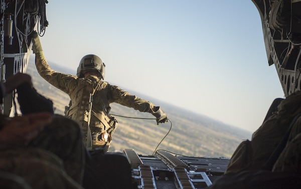 An Army aircrewman sits at the edge of a CH-47 Chinook helicopter during transit from Baghdad International Airport, April 20, 2016. DoD photo by Navy Petty Officer 2nd Class Dominique A. Pineiro