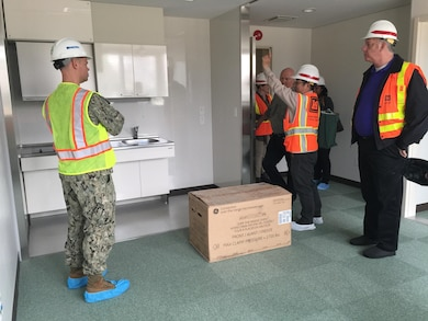 Kuniaki Nakamoto, U.S. Army Corps of Engineers Japan District Marine Corps Air Station Iwakuni Resident Office engineer, center, explains the layout of the kitchens in the new rooms of the Kintai Inn to Commander Jeffrey Pfeil, Facilities commander and Lawrence Seeba, Iwakuni Resident Office resident engineer.