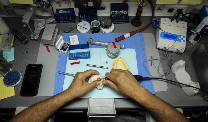 Edward Ibarra, a dental laboratory technician with the 1st Special Operations Dental Squadron, refines an implant at Hurlburt Field, Fla., April 18, 2016. The dental laboratory creates mouth appliances for patients prescribed by the dentists. Appliances may be permanent or removable depending on the treatment plan. (U.S. Air Force photo by Senior Airman Meagan Schutter)