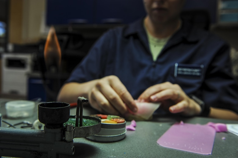 Staff Sgt. Kristina Plunkett, a dental laboratory technician with the 1st Special Operations Dental Squadron, shapes wax to a custom tray at Hurlburt Field, Fla., April 18, 2016. This four-manned laboratory cares for more than 40 patients every month. (U.S. Air Force photo by Senior Airman Meagan Schutter)