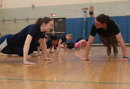 (Right)United States Marine Corps Pfc. Dayle M. Taber, a Hilton, N.Y., native and recent recruit training graduate, teaches push-up techniques to female Delayed Entry Program enlistees during an All-Female Pool Function in Rochester, N.Y., April 9, 2016. Taber motivated and shared her boot camp experiences with the future female Marines during the function. (U.S. Marine Corps photo by Staff Sgt. Christopher O'Quin/Released)