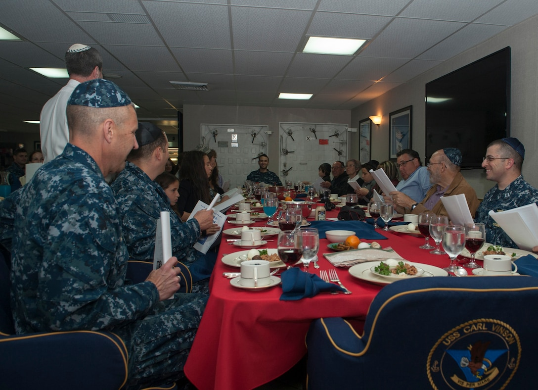 Sailors and family members participate in the Passover Seder meal aboard aircraft carrier USS Carl Vinson April 15, 2015. Jewish military members around the world can have a traditional Seder meal and observe Kosher during Passover, thanks to DLA Troop Support.