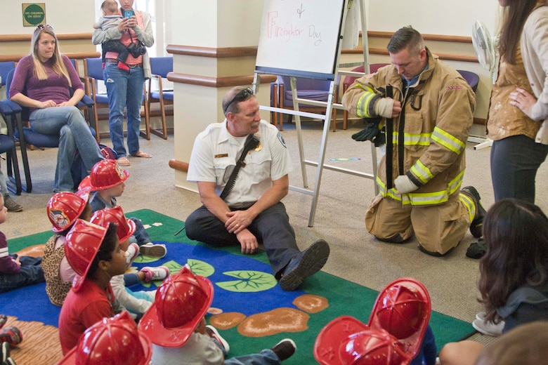 Stephen Williams, firefighter in Quantico Fire Station 531, shows a room full of toddlers a real firefighter suit during toddler story time.