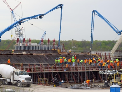 Olmsted Locks and Dam conducts a concrete placement on its eighth Nav Pass shell.  While crews move the blue 'tubes' to ensure concrete is filled in all the holes, other workers move and smooth the concrete to make sure it is at the proper height and level before the material hardens. The placement is the second of five lift placements. NP-8 is scheduled to be set October 18.