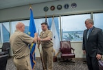 Navy Rear Admiral John King passes the organization's flag to Navy Capt. Justin Debord, chief of staff, as he relinquishes command of DLA Land and Maritime to James McClaugherty (right). McClaugherty will serve as acting commander until the newly-identified Navy Rear Admiral Michelle Skubic arrives on station.
