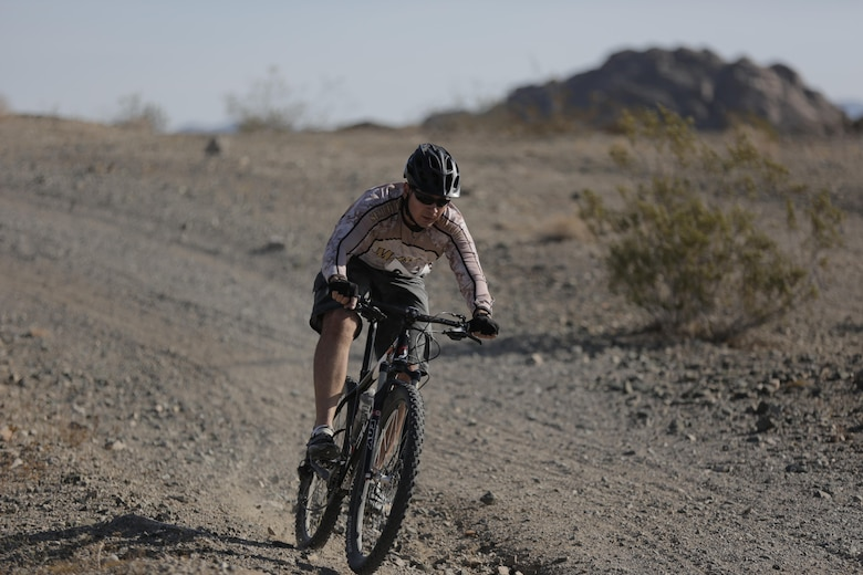 Sam Crabtree, tank mechanic, Exercise Support Division, speeds downhill during the Annual Earth Day Mountain Bike Ride held near Range 100 aboard the Combat Center April 13, 2016. The eight-mile ride started at Range 100 and took participants through designated trails behind the range. (Official Marine Corps photo by Pfc. Dave Flores/Released)
