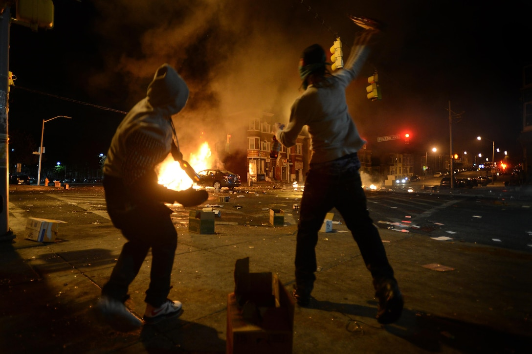 News: Young men throw bottles of beer at burning vehicles as a riot ensues after the funeral of Freddie Gray in Baltimore, April 27, 2015. Gray died April 19 from a severe spinal injury that allegedly occurred while in police custody. Looting and riots broke out in Baltimore after the funeral. The Maryland governor declared a state of emergency. Air Force photo by Staff Sgt. Kenny Holston