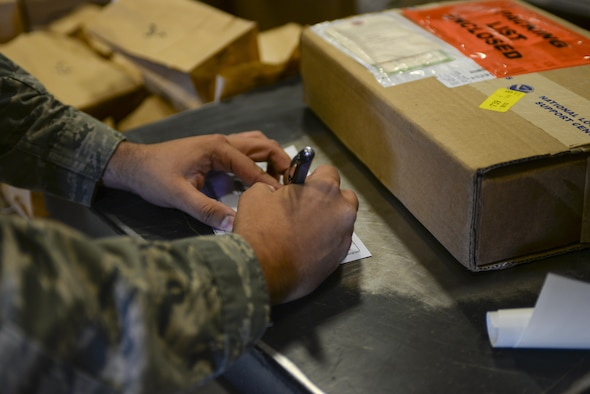 Senior Airman Thiago Gandarillas, 99th Logistics Readiness Squadron acting NCO in charge of planning and packaging, fills out a form while preparing a package for shipment at Nellis Air Force Base, Nev., on April 18, 2016. With over 40 percent of traffic management personnel deployed at all times, this team thrived through expert training and cross-utilization of talents to help with mission support, readiness and made significant and lasting contributions to the Nellis AFB, Creech AFB and Nevada Test and Training Range team as well as to the U.S. Air Force Warfare Center mission. (Air Force photo by Airman 1st Class Nathan Byrnes)