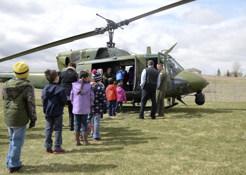 Children from Freedom Elementary School, Cheyenne, Wyo., line up to view one of the 37th Helicopter Squadron UH-1N Bell Helicopter April 20, 2016. Several dozen children were able to view the helicopter and have their questions answered by the crew.