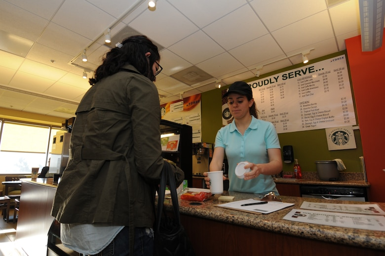 Andrea Murano, barista and food service worker, serves a customer at the newly opened Starbucks We Proudly Serve coffee shop at Schriever Air Force Base, Colorado, Thursday, April 21, 2016. The shop offers coffee, tea and limited food items and is open Monday through Friday, 7 – 11 a.m. (U.S. Air Force photo/2nd Lt. Darren Domingo)