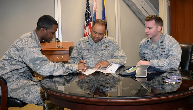 Lt. Gen. Samuel Greaves, Space and Missile Systems Center commander and Air Force program executive officer for space, signs his Air Force Assistance Fund pledge form as Capt. Rey Heron (left), SMC Financial Management cost analyst and AFAF project officer and Capt. Robert Wilcox, SMC Commander's Action Group officer look on. Now in its 44th year, this year's AFAF campaign kicked off March 21 and runs through April 29. The annual fundraising drive benefits four official Air Force charities: the Air Force Aid Society, Air Force Village Foundation, Air Force Enlisted Village, and the General and Mrs. Curtis LeMay Foundation. (U.S. Air Force photo/Van De Ha)