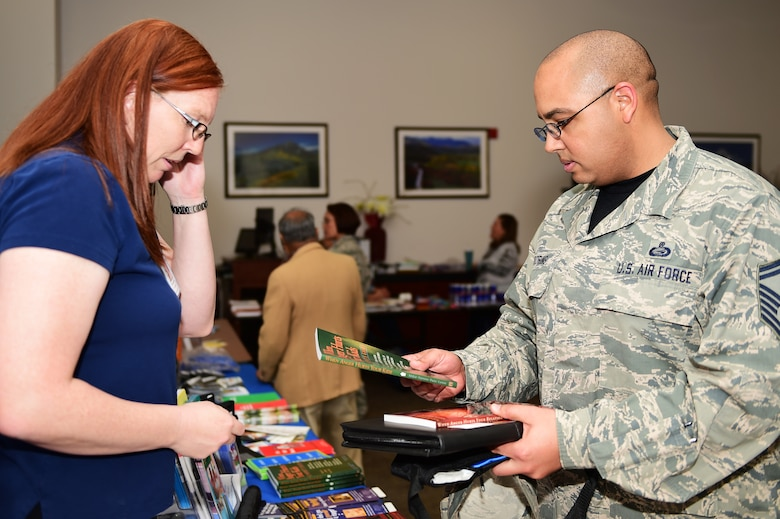 Senior Master Sgt. Crumel Mooring, 460th Space Wing Equal Opportunity superintendent, receives books from Christine Baird, 460th Medical Group family advocacy nurse, during a Child Abuse Awareness Month information fair April 15, 2016, on Buckley Air Force Base, Colo. All children deserve to grow up in a caring and loving environment, yet in the United States, hundreds of thousands of children are neglected or abused each year, often causing lasting consequences with between four and eight children dying every day from abuse or neglect. (U.S. Air Force photo by Senior Airman Racheal E. Watson/Released)
