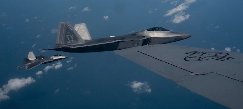 Two U.S. Air Force 95th Fighter Squadron F-22 Raptors from Tyndall Air Force Base, Fla., fly alongside a 100th Air Refueling Wing KC-135 Stratotanker assigned to RAF Mildenhall, England, April 19, 2016, over the Norfolk Sea. The fifth generation, multi-role fighter aircraft participated to maximize training opportunities, affirm enduring commitments to NATO allies, and deter any actions that destabilize regional security. (U.S. Air Force photo by Senior Airman Victoria H. Taylor/Released)