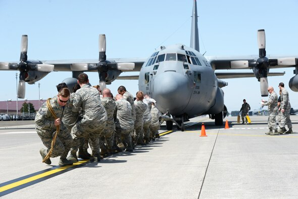 Members with the 374th Maintenance Squadron pull a C-130 Hercules at Yokota Air Base, Japan, April 15, 2016. The aircraft was pulled as part of the 374th Maintenance Group's Maintenance Rodeo Competition, which pits squadrons against each other in various tasks to win points toward an award and bragging rights. (U.S. Air Force photo/Staff Sgt. Cody H. Ramirez)