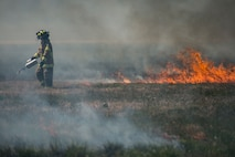 An Air Force firefighter assigned to the 633rd Civil Engineer Squadron ignites a fire during a controlled burn at Langley Air Force Base, Va., April 17, 2016. The burn prepared for the upcoming AirPower over Hampton Roads Open House fireworks show. (U.S. Air Force photo/Senior Airman Kayla Newman)