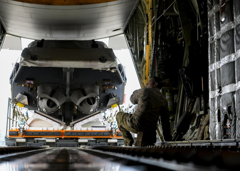 U.S. Air Force Master Sgt. Lino Gato, a 67th Special Operations Squadron MC-130J Commando II loadmaster, kneels ready to receive a large Rigid Inflatable Boat approaching the aircraft during an exercise April 14, 2016, at Stuttgart Air Base, Germany. A total of 79,000 pounds of cargo were carried between the two aircraft deployed from the 67th SOS. (U.S. Air Force photo by Senior Airman Victoria H. Taylor/Released)