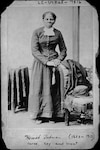 Harriet Tubman, full-length portrait, standing with hands on back of a chair. Between ca. 1860 and 1875.