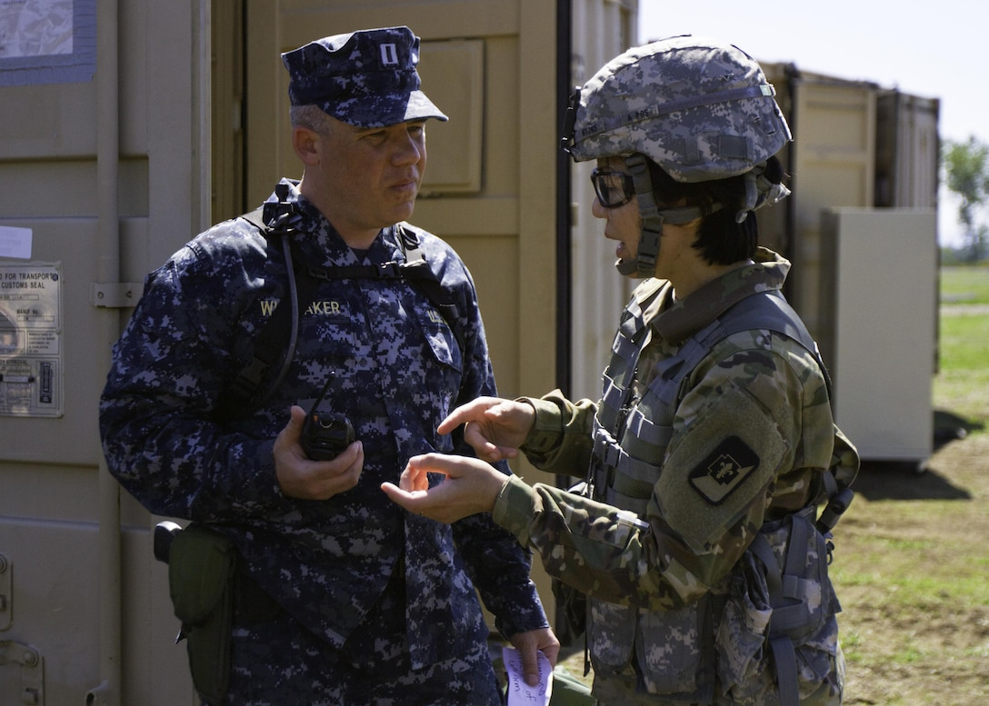 Navy Capt. Beecher Whiteaker, a dentist with Naval Hospital Oak Harbor, Washington, recieves guidance from Col. Christensen Hsu, commander of the 673rd Dental Company, 62nd Medical Brigade, 593rd Expeditionary Sustainment Command, during a total force integrated training exercise at Joint Base Lewis-McChord, Washington, April 18-29, 2016. Dental professionals with the Army, Army Reserves and Navy came together to perform dental care in a deployed environment during the exercise. (U.S. Army photo by Sgt. Cody Quinn/28th Public Affairs Detachment)
