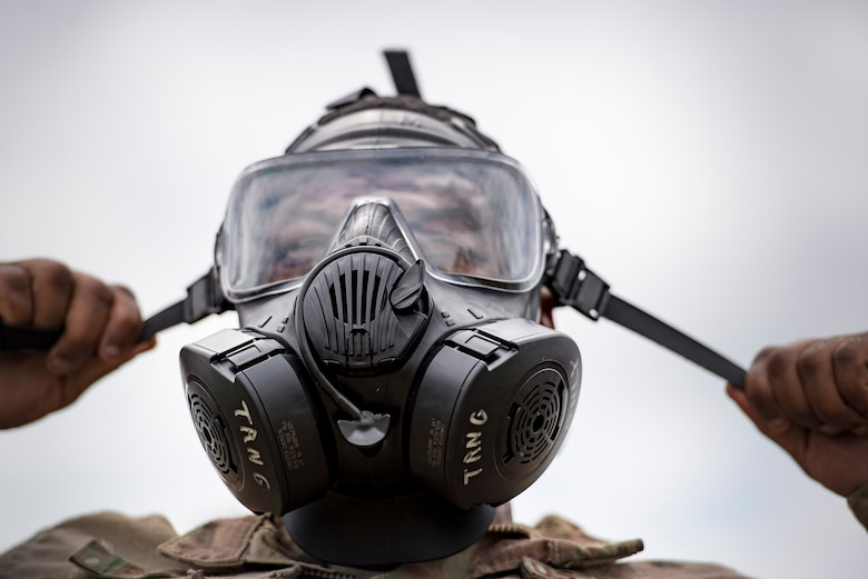 U.S. Air Force Senior Airman Eric Purnell, 823d Base Defense Squadron fireteam member, tightens a gas mask, April 13, 2016, Avon Park Air Force Range, Fla. Part of the obstacle course challenge involved dressing in full mission-oriented-protective-posture gear and being cleared by cadre before moving on to the next obstacle. (U.S. Air Force photo by Airman 1st Class Janiqua P. Robinson/Released)