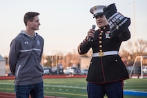 Staff Sgt. David Hall, a recuiter with Recruiting Station Denver, motivates the crowd at a high school soccer game while standing next to Porter Milner, a Broomfield High School athlete and senior, during the Sports Illustrated Athlete of the Month presentation at Broomfield High School, April 21, 2016. Milner received the award not just for his athletic skills, but also his dedication to leadership, camaraderie and personal development.
