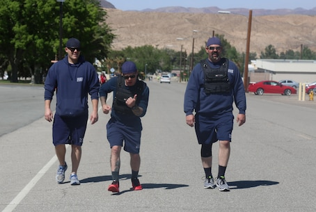 Shaun Longlee and David Pacileo, firefighters, work to keep up with Lt. Joseph Haresky, setting the bar high for Security and Emergency Services during the No More 5K aboard Marine Corps Logistics Base Barstow, Calif., April 15. The event drew awareness to domestic violence and sexual assault prevention.