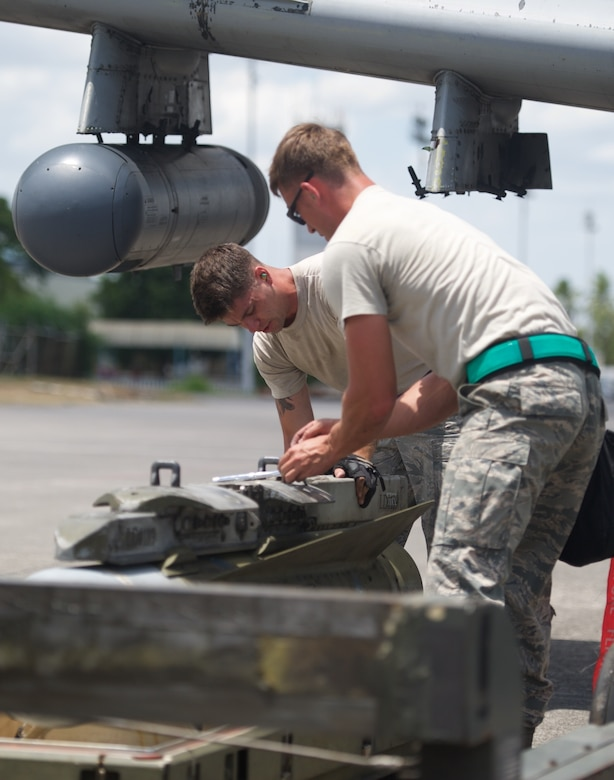 U.S. Air Force Staff Sgt. Kyle Whetham, weapons load crew chief, and Senior Airman Jonathan Simmons, weapons load crew member, inspect a training round from an A-10C Thunderbolt II after the aircraft completed a maritime domain awareness mission in the vicinity of Scarborough Shoal west of the Philippines April 21, 2016. These missions are intended to provide more transparent air and maritime situational awareness to ensure safety for military and civilian activities in international waters and airspace, and as such, the aircraft do not carry live rounds. Whetham and Simmons are deployed to Clark Air Base, Philippines from Osan Air Base, Republic of Korea. (U.S. Air Force photo by Capt. Susan Harrington)