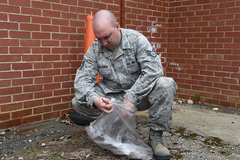 Staff Sgt. John Lewellyan, 89th Aerial Port Squadron passenger service supervisor, picks up garbage around the flight line and passenger terminal at Joint Base Andrews, Md., April 22, 2016. Team Andrews cleaned up around base in commemoration of Earth Day. (U.S. Air Force photo by Senior Airman Joshua R. M. Dewberry/RELEASED)