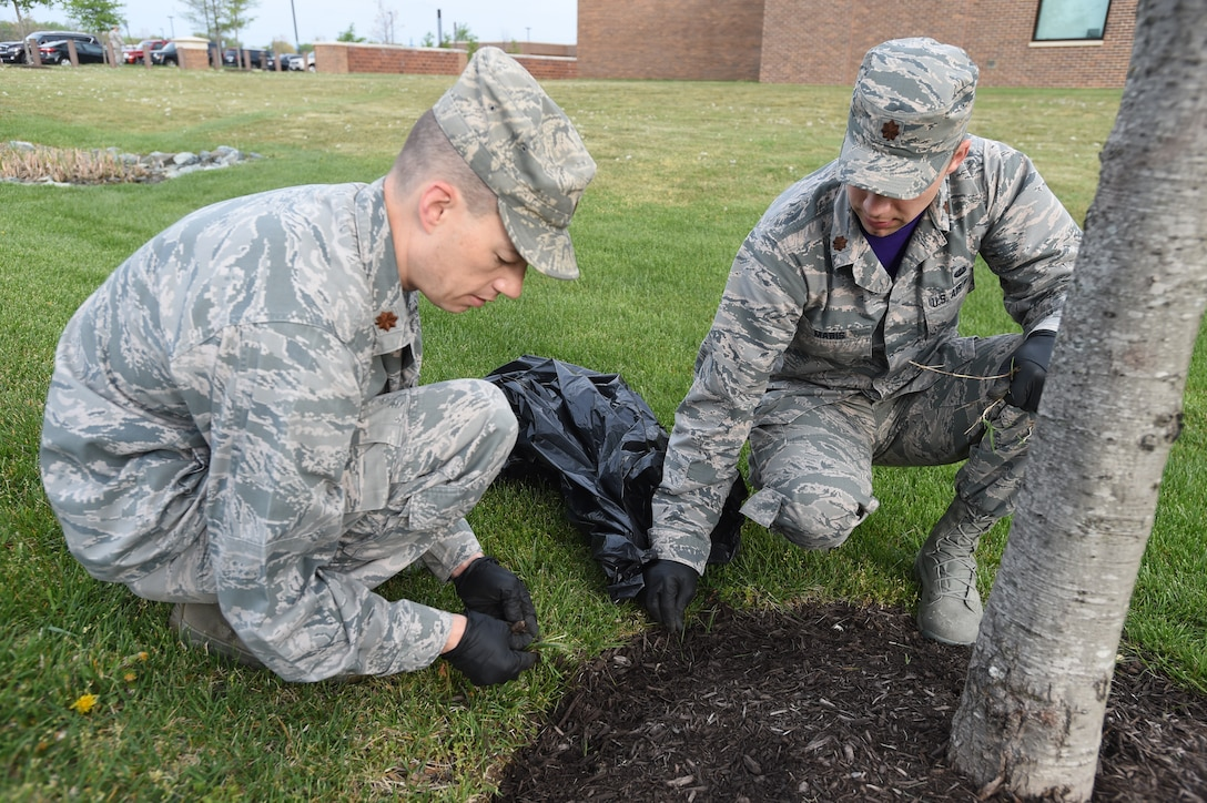 Maj. Michael Hopkins (left), Air Force Legal Operations Agency Special Victims Counsel Program deputy division chief, and Maj. Kurt Mabis (right), AFLOA Civil Law and Litigation directorate executive, pick weeds around the Jones building at Joint Base Andrews, Md., April 22, 2016. Team Andrews cleaned up around base in commemoration of Earth Day. (U.S. Air Force photo by Senior Airman Joshua R. M. Dewberry/RELEASED)