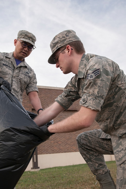 Tech. Sgt. James Aguilar, 11th Comptroller Squadron customer service technician and Senior Airman Josh Ulrich, 11th CPTS payroll technician, work together to dispose of litter at Joint Base Andrews, Md., April 22, 2016. The Airmen assisted with the base-wide clean up in commemoration of Earth Day. (U.S. Air Force photo by Airman Gabrielle Spalding/Released)