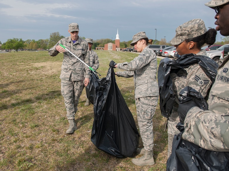 Airman 1st Class Darlena Vazques Quinones, 11th Comptroller Squadron military pay technician, assists Airman 1st Class Joseph Violette, 11th CPTS travel technician, with disposing trash at Joint Base Andrews, Md., April 22, 2016. The Airmen assisted with the base-wide clean up in commemoration of Earth Day. (U.S. Air Force photo by Airman Gabrielle Spalding/Released)