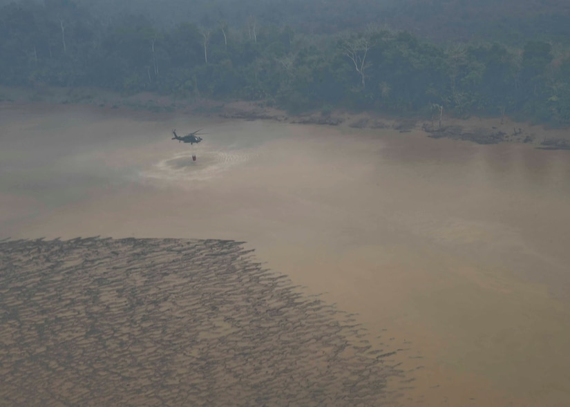 A UH-60 Black Hawk assigned to the 1st Battalion, 228th Aviation Regiment, Joint Task Force Bravo at Soto Cano Air Base, Honduras, refills a Bambi Bucket in a river during a firefighting operation in the Darién province of Panama, April 18, 2016. After each pass and dump, the 1-228th AVN air assets refilled their Bambi Buckets in one of the area's many bodies of water. (U.S. Air Force photo by Staff Sgt. Siuta B. Ika)