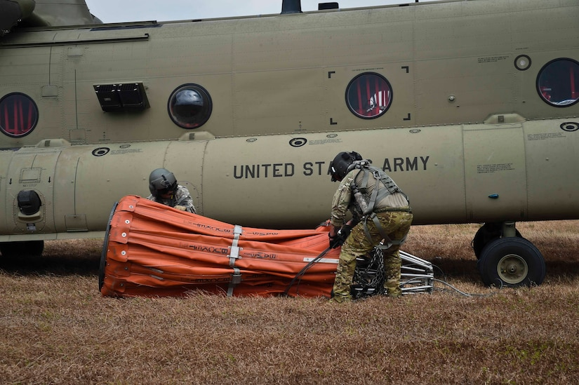 U.S. Army Staff Sgt. John Fajota and Sgt. 1st Class Christopher Gagnon, both CH-47 Chinook crew members assigned to the 1st Battalion, 228th Aviation Regiment, prepare to connect a Bambi Bucket to a Chinook for a firefighting operation in the Darién province of Panama, April 18, 2016. The air assets of the 1-228th AVN dropped approximately 100,000 gallons of water during the firefighting operation. (U.S. Air Force photo by Staff Sgt. Siuta B. Ika)