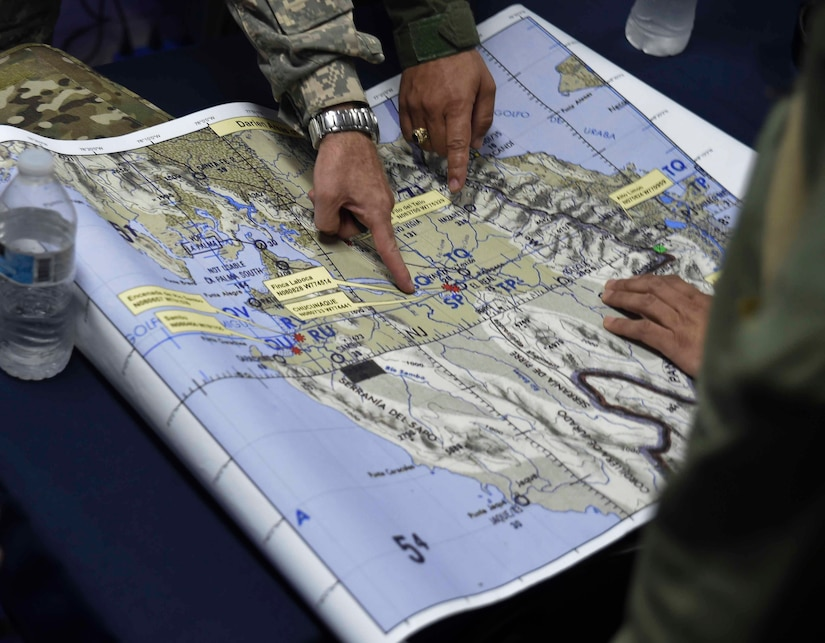 Members of the Panamanian Public Forces and the 1st Battalion, 228th Aviation Regiment, a unit assigned to Joint Task Force Bravo at Soto Cano Air Base, Honduras, discuss operational details before fighting wildfires in the Darién province of Panama, April 17, 2016. The real-world operation provided an opportunity for U.S. and Panamanian forces to work closely together outside of a training environment, such as CENTAM SMOKE, or Sharing Mutual Operational Knowledge and Experiences, a semi-annual firefighting exercise hosted at Soto Cano AB. (U.S. Air Force photo by Staff Sgt. Siuta B. Ika)