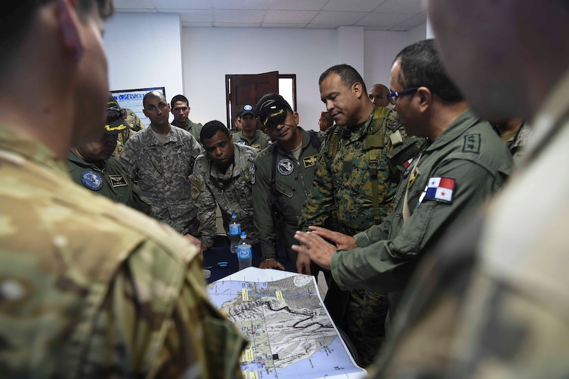Members of the Panamanian Public Forces and the 1st Battalion, 228th Aviation Regiment, a unit assigned to Joint Task Force Bravo, Soto Cano Air Base, Honduras, discuss operational details before fighting wildfires in the Darién province of Panama, April 17, 2016. During the operation, Panamanian and U.S. command and control elements reviewed inputs from the ground forces and surveillance from air assets to determine where the fire, which had split into hundreds of separate fires, needed the most attention. (U.S. Air Force photo by Staff Sgt. Siuta B. Ika)